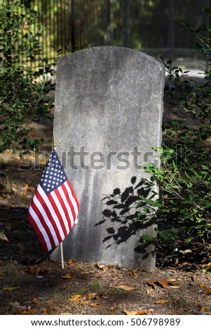 Tall rectangular tombstone, blank for copy space. A small American flag and a green bush are at the base of the stone.