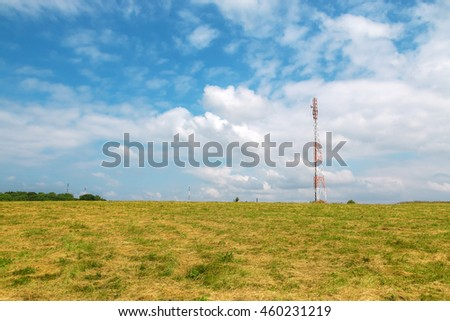 Tall red and white cellular tower in the green field