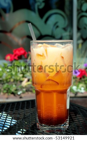 Tall refreshing glass of icy cold Thai iced tea with straw - stock photo