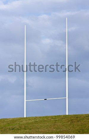 Tall rugby union goal posts and cloudy blue skies - stock photo