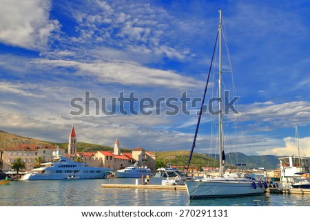 Tall sail boat anchored inside sunny harbor of old Venetian town, Trogir, Croatia - stock photo