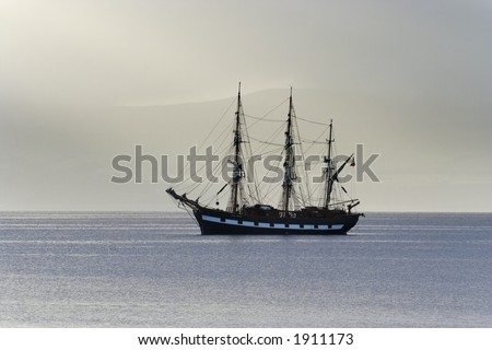 Tall ship anchored in a calm sea lit by morning light - stock photo