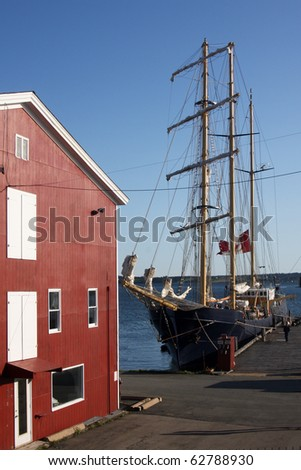 Tall Ship at Pier with Red Warehouse