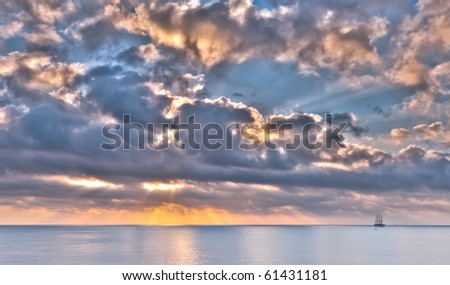 Tall ship on horizon against dramatic sunset sky - stock photo
