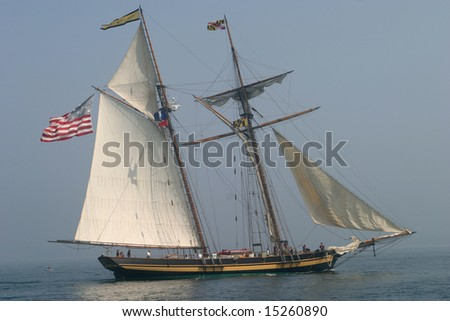 Tall ship sailing against a foggy background. - stock photo