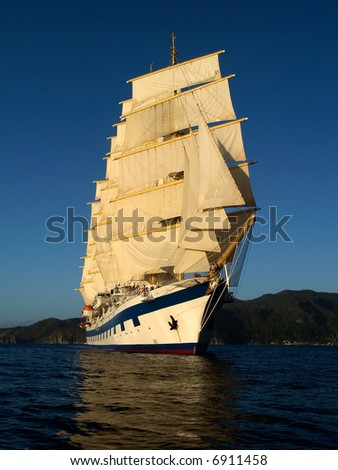 Tall ship under full sails in the light of evening sun