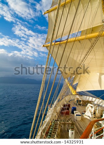 Tall ship under full sails in the sea moving to the island