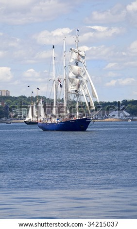 Tall ships sailing around Halifax Harbour during the sail past in the Nova Scotia Tall Ship Festival. - stock photo