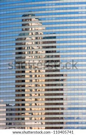 tall skyscraper reflected in modern building mirror glass wall - stock photo