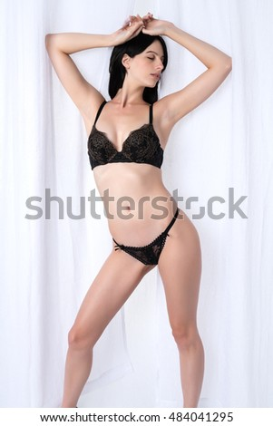 Tall slender brunette dressed in black lingerie