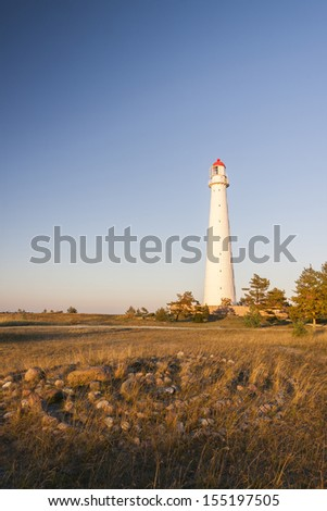 Tall slim white beacon or lighthouse known as Tahkuna at sunset in Hiiumaa, Estonia and stone labyrinth or maze in foreground.  - stock photo
