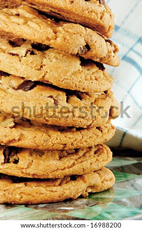 Tall stack of chocolate chip cookies fresh from the oven. - stock photo