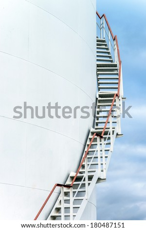Tall staircase to big oil tank in refinery - stock photo