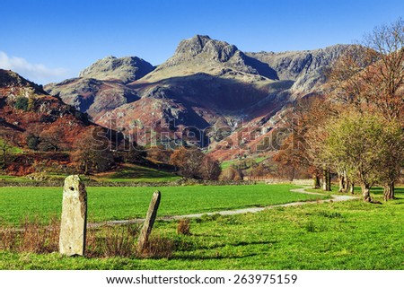 Tall stones by the road to the Langdale Pikes. A couple of interesting stones stand by the path towards the magnificent Langdale Pikes as seen on a sunny autumn day. - stock photo