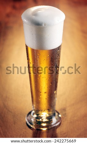 Tall stylish glass of refreshing chilled beer with a good frothy head on a wooden background with vignette, high angle view - stock photo