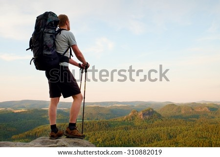 Tall tourist with poles in hand. Sunny evening in rocky mountains. Hiker with big backpack stand on rocky view point above misty valley.  - stock photo