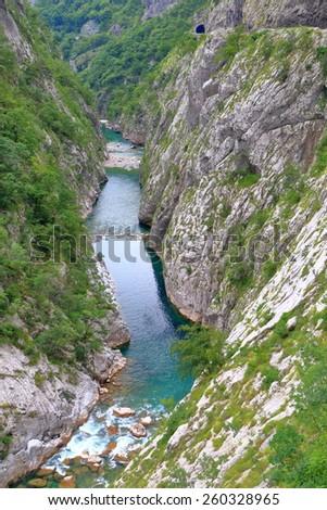 Tall walls of a canyon above deep narrow river - stock photo