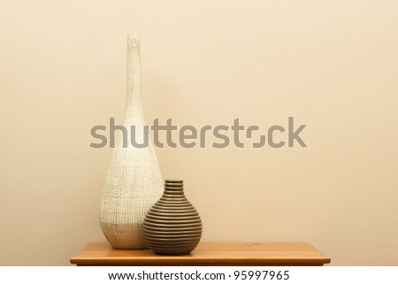 Tall white vase and short striped vase still life - horizontal - stock photo