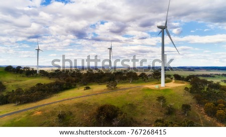 Tall wind powered energy genecating turbines with properllers as part of wind farm on top of hill range in rural under cloudy sky.