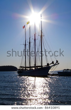 Tall wind sailing schooner at dock back lit by rising sun - stock photo