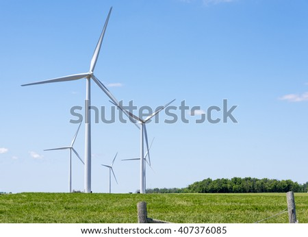Tall wind turbines stand majestically in a field in southwest Ontario Canada. - stock photo