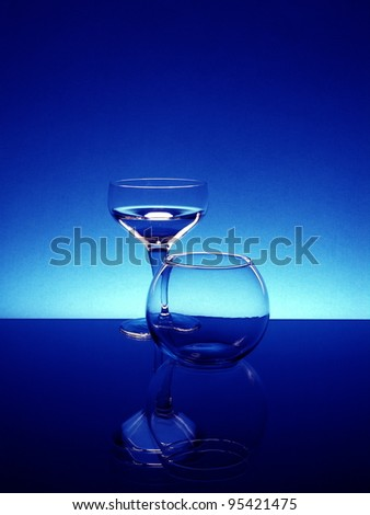 Tall wineglass and a flower bowl against a dark blue background - stock photo