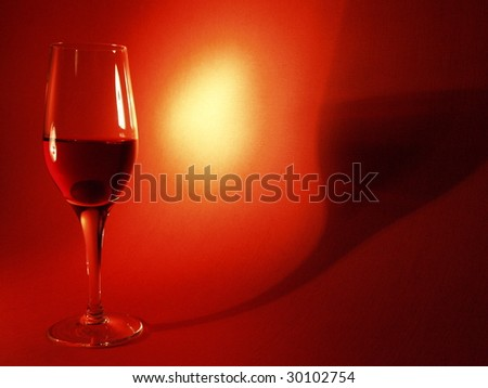 Tall wineglass with an olive against a red background - stock photo