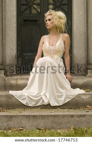 Tall woman in white dress sitting outside on the steps looking to the left - stock photo