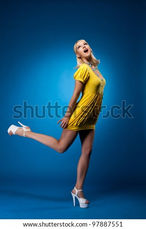 Tall woman in yellow sexy dress jump on blue - stock photo