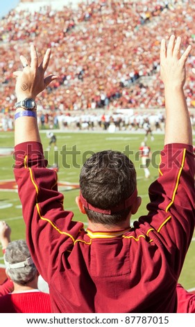 TALLAHASSEE, FL - OCT. 22:  Florida State football fan stands up and cheers at a home game as the FSU Seminoles play the Maryland Terps at Doak Campbell Stadium on Oct. 22, 2011. - stock photo