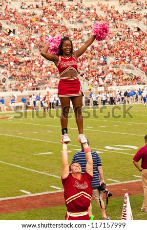 TALLAHASSEE, FL - OCT. 27:  Florida State male cheerleader supports a female cheerleader during a FSU vs Duke University football game at Doak Campbell Stadium on Oct. 27, 2012. - stock photo