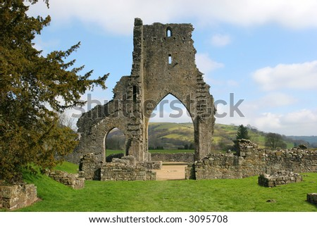 Talley Abbey monastery ruins with rural countryside beyond the main arch and grass in the foreground. Set against a pale blue sky with clouds.
