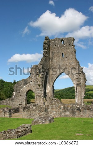 Talley Abbey ruins in Wales, United Kingdom, with rural countryside beyond the main arch and grass to the foreground. Set against a blue sky with clouds.