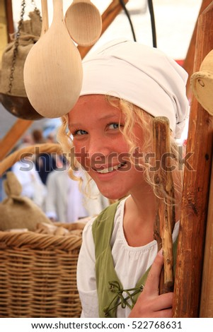 TALLINN, ESTONIA - JUNE, 3: An unknown beautiful young, blonde girl dressed in period costume at a medieval fair in the old town - a UNESCO World Heritage Site. On June 3, 2008 in Tallinn, Estonia.