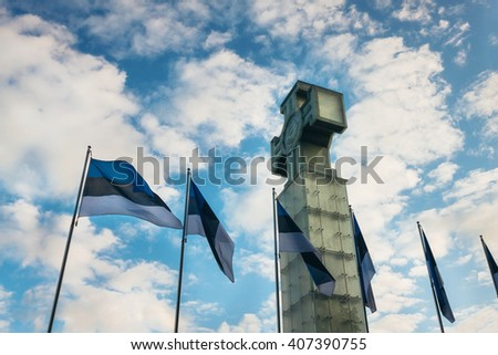TALLINN, ESTONIA - JUNE 30, 2013: Scenic view of The Cross of Liberty Vabadusrist and estonian flags at sunset. Estonian war of independence memorial Eesti Vabadus Soda. - stock photo