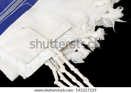 Tallit, Jewish prayer shawl. White wool cloth garment with knots and fringes worn by Jewish men during prayer services. Blue stripes indicate Sephardic style and custom. Isolated on a black background - stock photo