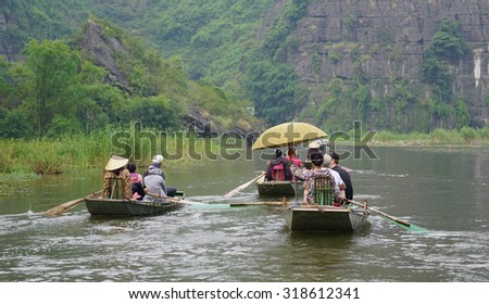Tam Coc, Vietnam - Sep 3, 2015. People rowing boats for carrying tourists in Tam Coc National Park. Tam Coc is a popular tourist destination near the city of Ninh Binh in northern Vietnam.