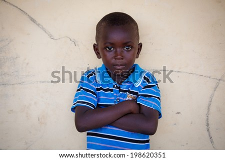 TAMALE, GHANA - MARCH 22: Unidentified young African boy pose and look at camera on March 22, 2014 in Tamale, Ghana. Tamale is the hub of all commercial activity in Northern Region of Ghana.