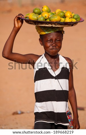 TAMALE, GHANA - MARCH 22: Unidentified young african girl carry fruits on her head on March 22, 2014 in Tamale, Ghana. Carrying things on head is general skill of African girls and women. - stock photo
