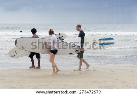 TAMARINDO, COSTA RICA - SEPTEMBER 13, 2008: Surfers walking on the beach of Tamarindo, Costa Rica. Tamarindo is located on the Northern Pacific Coast and is a leading surfer hotspot. - stock photo