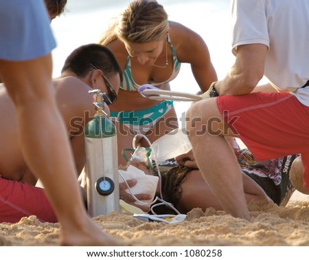 Tamayo Perry, a world class big wave surfer, is treated on the beach after being injured while surfing the Bonzai Pipeline surf break on Oahu's North Shore. (image contains noise) - stock photo