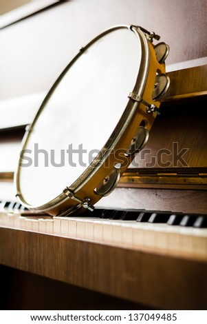 Tambourine on piano keys. Musical concept.