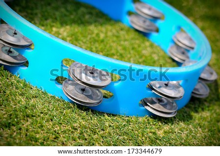 Tambourine percussion isolate on the green grass - stock photo