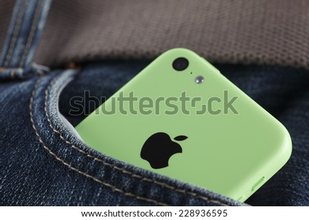 Tambov, Russian Federation - October 16, 2013: Apple iPhone 5C Green Color in a pocket of jeans. Studio shot. iPhone 5C is produced by Apple Computer, Inc. - stock photo