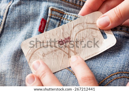 Tambov, Russian Federation - October 21, 2012 Woman's hand taking label logo with phrase 'Quality never goes out of style' on the pair Levi's Jeans. Studio shot.
