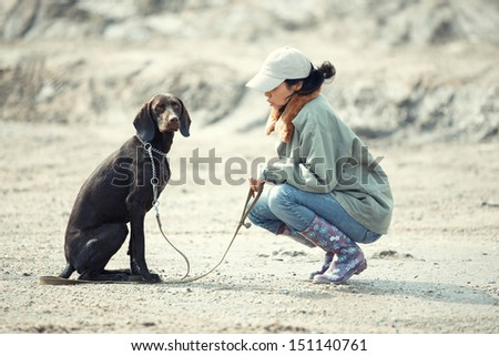 Tamer sitting with German short haired pointer outdoors - stock photo