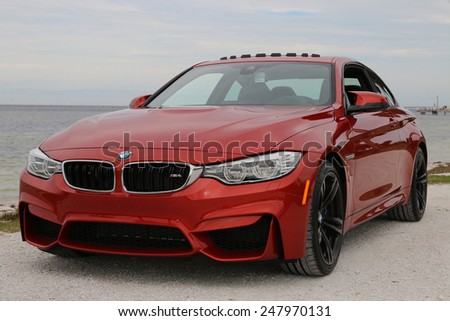 TAMPA, FLORIDA/USA - JANUARY 18 2015: The brand new 2015 BMW M4 parked near a beach in Tampa, FL. This Sakhir Orange M4 has a 6 cylinder twin turbo engine as well as the upgraded 19 inch black wheels. - stock photo