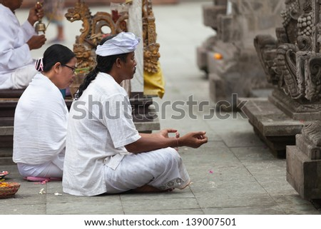 TAMPAK SIRING, BALI, INDONESIA - SEP 21: People praying at holy spring water temple Puru Tirtha Empul during the religious ceremony on Sep 21, 2012 in Tampak Siring, Bali, Indonesia