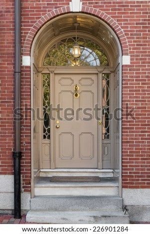 Charmant Tan Front Door With Lunette Window And Arch In Brick Building With Pipe
