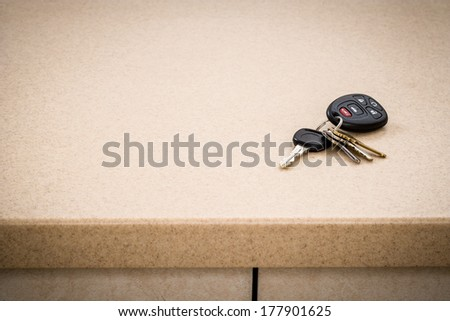 Tan kitchen counter with automotive car keys - stock photo